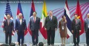 picture of ASEAN country representatives standing before their flags
