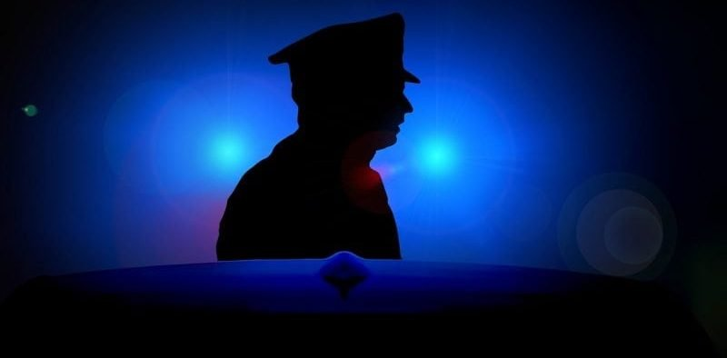Blue light surrounds the silhouette of a police officer.