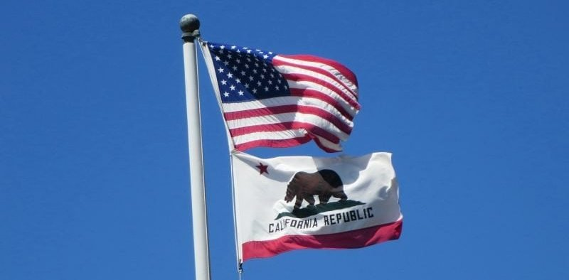 Image of US flag and California flag against blue sky