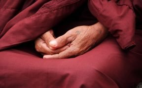 image of a monks folded hands in a red robe