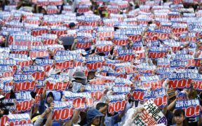 Protestors gather and hold up signs to protest the location of a US military base in Henoko Bay, Okinaw