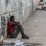 Photo of an impoverished African man sitting on the street.