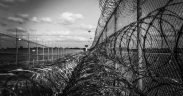 Image of barbed wire along a prison fence