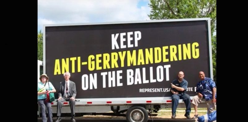 """Volunteers pose before a Represent.Us sign saying """"keep anti-gerrymandering on the ballot"""""""