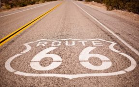 Route 66 sign on empty paved road