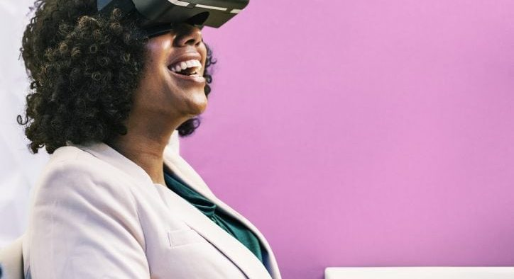 Photo of a woman sitting at a desk with a virtual reality headset on