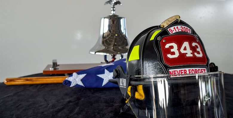 photo of a fireman's hat laid over an American flag