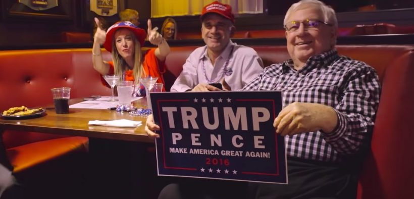 Screenshot of Trump supporters holding Trump Pence sign at a diner
