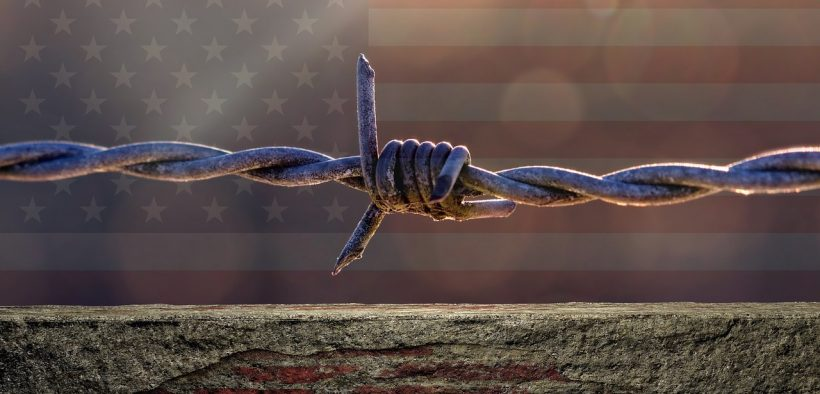 photo of American flag with a barbed wire and wall in front of it. The ACLU released a report condemning the expansion of the US Mexico border wall.