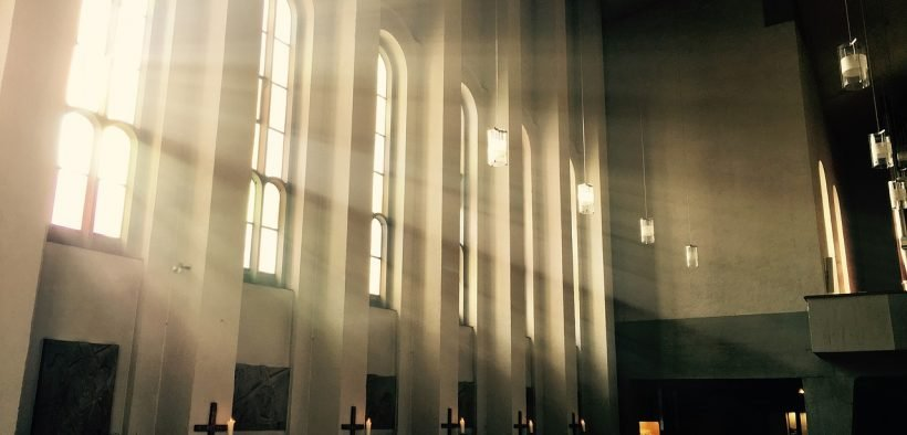Photo of light streaming in through a Catholic Church.