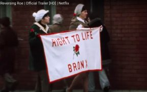 Screenshot from Reversing Roe of women in the Bronx marching with a Right to Life banner