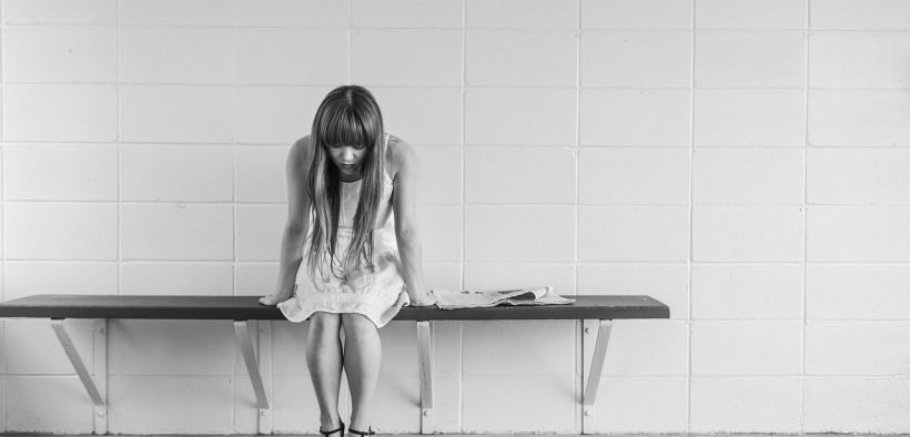 Image of a sad looking woman sitting on a bench. Sexual assault survivors.