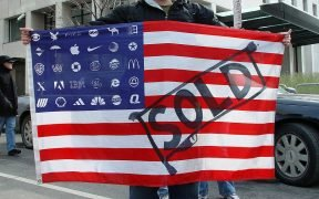 Protestor carrying U.S. flag with SOLD written on it and corporate logos in place of stars. The Equal Citizens lawsuit in Alaska is challenging dark money and super PACs created by the 2010 Citizens United ruling.