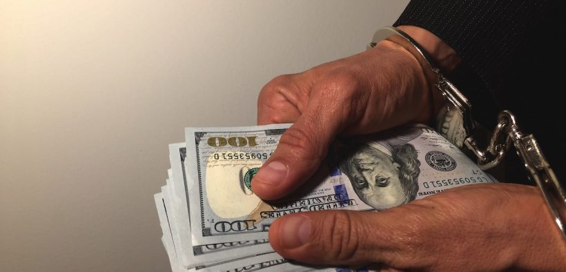 Man in handcuffs holding stack of money. The new S.W.A.M.P. Index ranks your state according to anti-corruption measures.