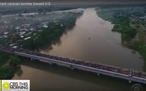 Honduran migrant caravan crossing a bridge