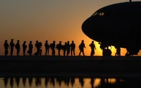 photo of soldiers lining up to board a military aircraft. US Presidents change, but the military-industrial complex never does.