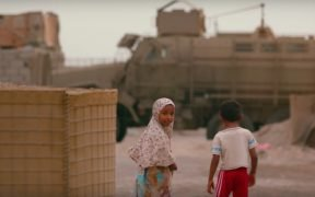 Children in Yemen walking around military equipment