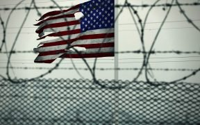 US flag behind a barbed wire fence