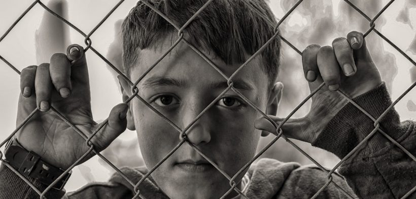 boy looking out behind wire fence