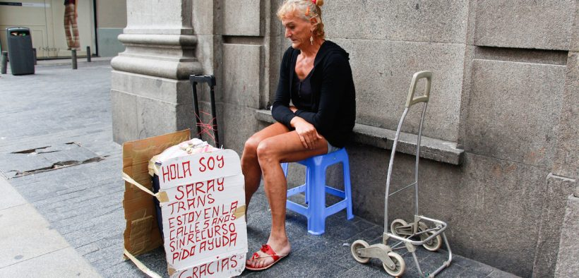 homeless woman in Spain with a sign asking for help