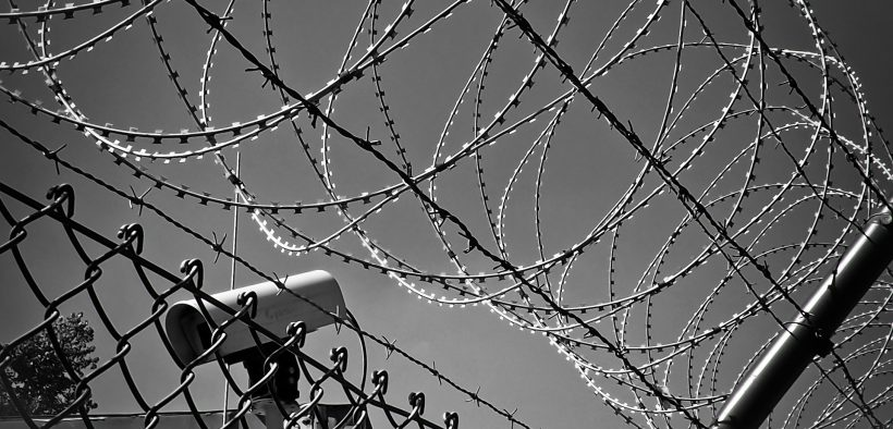 barbed wire and camera on a wall