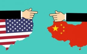 graphic of United states and China with hands pointing fingers at each other