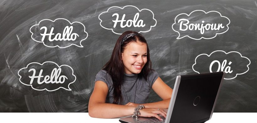"""student at a computer with chalkboard behind her. On the chalkboard it says """"hello, hola, ola, bonjour"""""""