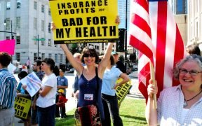 "protestor holding a sign saying ""insurance profits are bad for my health"""