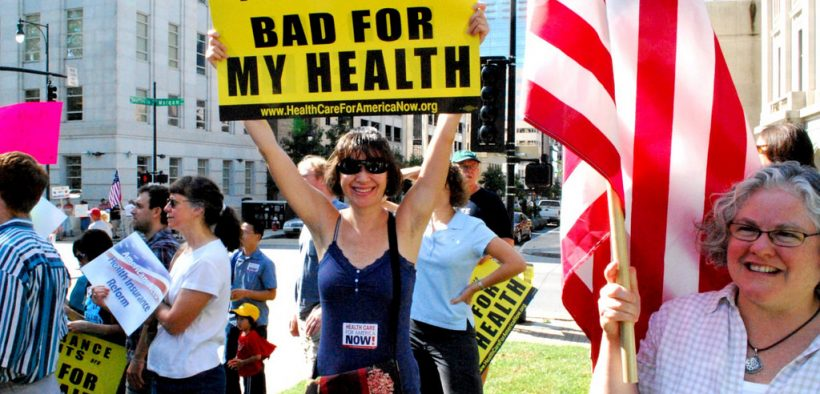 """protestor holding a sign saying """"insurance profits are bad for my health"""""""