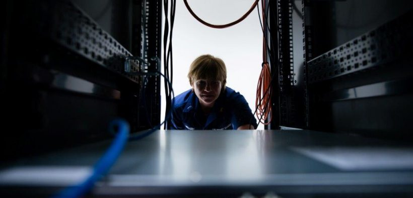 U.S. Coast Guard Chief Warrant Officer DeAnna Melleby, Information Systems Security Officer for the Coast Guard Command, Control, Communication and Information Technology unit at Coast Guard Base Boston, peers through a space in a server April 20, 2017.