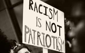 "protestor holding a sign that says ""Racism is not patriotism"""