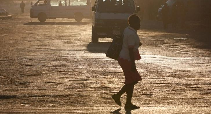 A woman crosses the street in front of minibus taxis in Harare, Zimbabwe, August 31, 2016. REUTERS/Philimon Bulawayo - S1AETYOPMLAA
