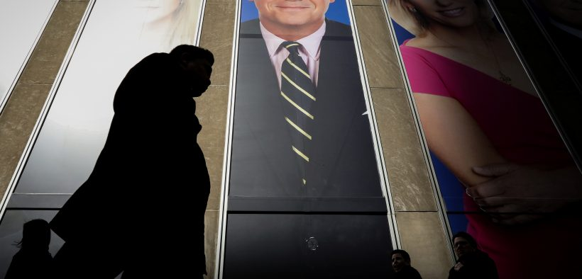 People pass by a promo of Fox News host Tucker Carlson on the News Corporation building in New York, U.S., March 13, 2019. REUTERS/Brendan McDermid