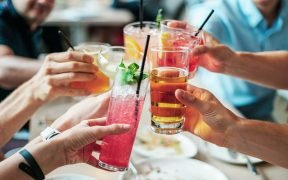photo of friends toasting alcoholic drinks, alcohol abuse in the US is an overlooked drug problem