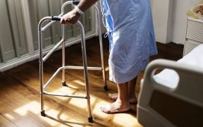 elderly person in hospital gown with a walker