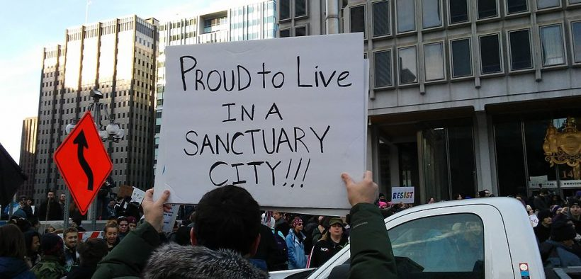 """Man holds a sign that says """"proud to live in a sanctuary city."""" On Saturday, February 4, 2017 the March for Humanity was held in Philadelphia to show support for immigration and refugees, among other things."""
