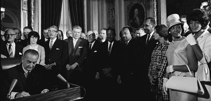 President Lyndon B. Johnson signs the Voting Rights Act of 1965 while Martin Luther King and others look on.
