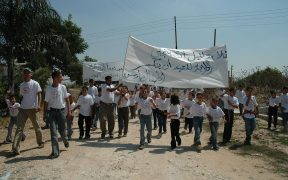 巴勒斯坦儿童在约旦河西岸抗议。 他们都穿着同样的白色衬衫,上面写着:占领的受害者要求正义,自由与和平