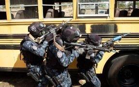 Os TIGRES hondurenhos saem ao lado de um ônibus escolar usado como um auxílio de treinamento localizado em uma área da Base Aérea de Eglin, em fevereiro de 27, 2015. O TIGRES, uma força antinarcóticos e de combate ao tráfico, estava participando de testes de exercício de culminação, testando as quase duas semanas de treinamento avançado que receberam dos soldados das Forças Especiais da 7th SFG (A). (Foto pelo capitão Thomas Cieslak)