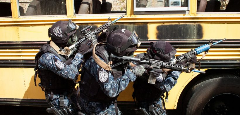 Honduran TIGRES clear along the side of a school bus used as a training aid located on an Eglin Air Force Base range Feb. 27, 2015,. The TIGRES, a counter-narcotic and counter-trafficking force, were participating in culmination exercise testing the nearly two weeks of advanced training they received from Special Forces soldiers of the 7th SFG (A). (Photo by Capt. Thomas Cieslak)