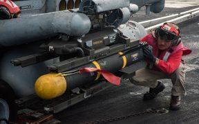 Sailor inspeciona a montagem de um míssil Hellfire em um helicóptero MH-60R Sea Hawk.
