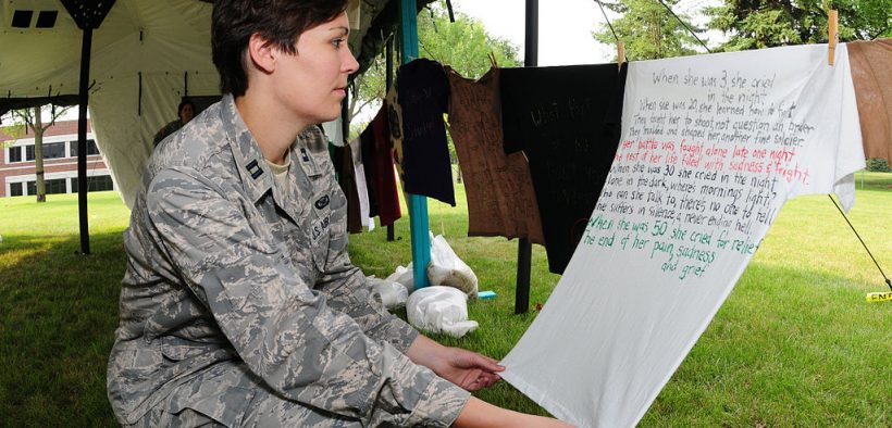 U.S. Air Force Capt. Penny Ripperger, the sexual assault response coordinator with the 119th Wing, North Dakota Air National Guard, reads a poem written on a T-shirt at a Clothesline Project visual display on the Veteran's Administration Hospital grounds in Fargo, N.D., July 29, 2010. The Clothesline Project display uses T-shirts created by victims of military sexual trauma to raise awareness and as part of the healing process.