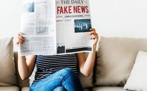 person holding a fake news newspaper