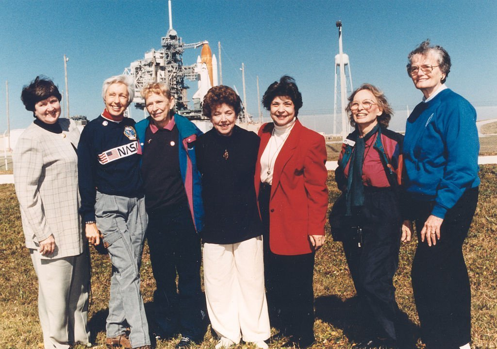 """Exuberant and thrilled to be at the Kennedy Space Center, seven women who once aspired to fly into space stand outside Launch Pad 39B neat the Space Shuttle Discovery, poised for liftoff on the first flight of 1995. They are members of the First Lady Astronaut Trainees (FLATs, also known as the """"Mercury 13""""), a group of women who trained to become astronauts for Americas first human spaceflight program back in the early 1960s. Although this FLATs effort was never an official NASA program, their commitment helped pave the way for the milestone Eileen Collins set: becoming the first female Shuttle pilot. Visiting the space center as invited guests of STS-63 Pilot Eileen Collins are (from left): Gene Nora Jessen, Wally Funk, Jerrie Cobb, Jerri Truhill, Sarah Rutley, Myrtle Cagle and Bernice Steadman."""