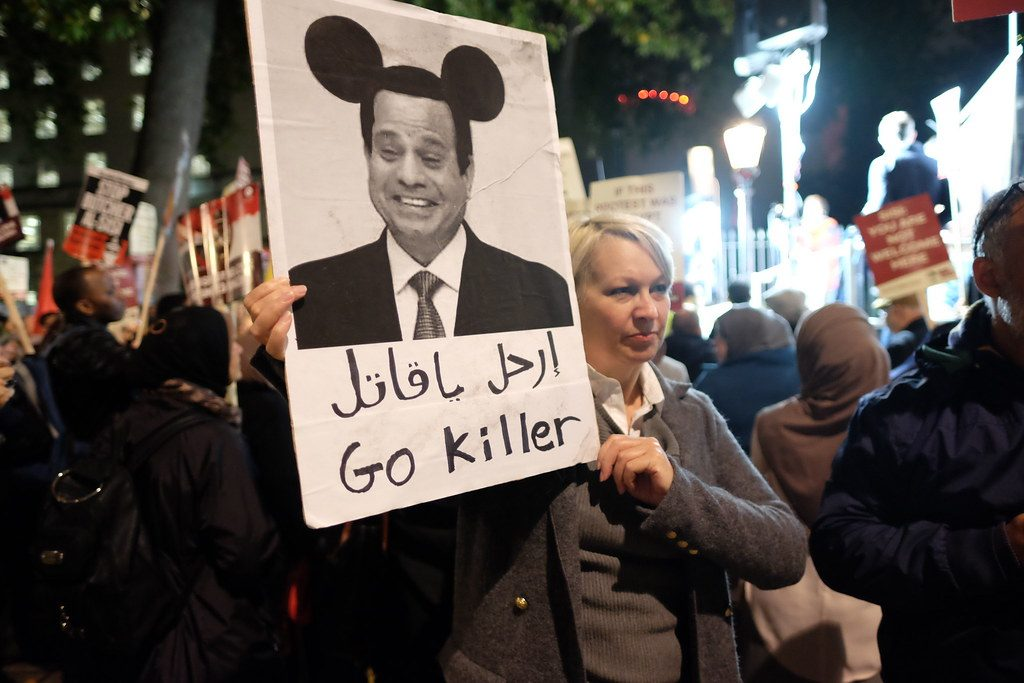 "An English woman was one of several British citizens who joined hundreds of Egyptian protesters angry at Britain's David Cameron rolling out the red carpet for Egypt's dictator Abdel Fatah el-Sisi. And why did she depict Sisi as ""Mickey Mouse"" ? Because just the previous month an Egyptian Facebook user had been sentenced to three years in prison for photoshopping a picture of Sisi and adding the mickey mouse ears."