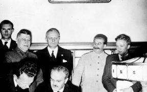O comissário estrangeiro soviético Vyacheslav Molotov assina o pacto de não-agressão soviético-alemão; Joachim von Ribbentrop e Josef Stalin estão atrás dele. Moscou, agosto 23. 1939.
