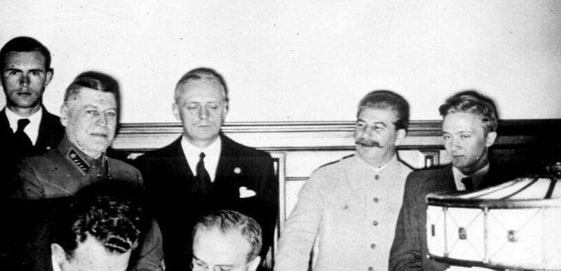 Советский министр иностранных дел Вячеслав Молотов подписывает германо-советский пакт о ненападении; Иоахим фон Риббентроп и Иосиф Сталин стоят за ним. Москва, август 23. 1939.