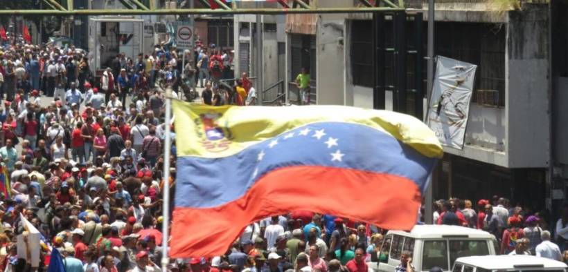 "A ""Hands Off Venezuela"" banner flies above a crowd at a pro-Maduro rally in Caracas, Venezuela."