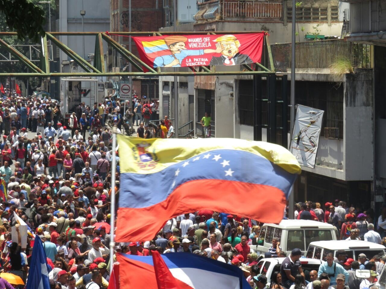 "A ""Hands Off Venezuela"" banner flies above a crowd at a pro-Maduro rally in Caracas, Venezuela."