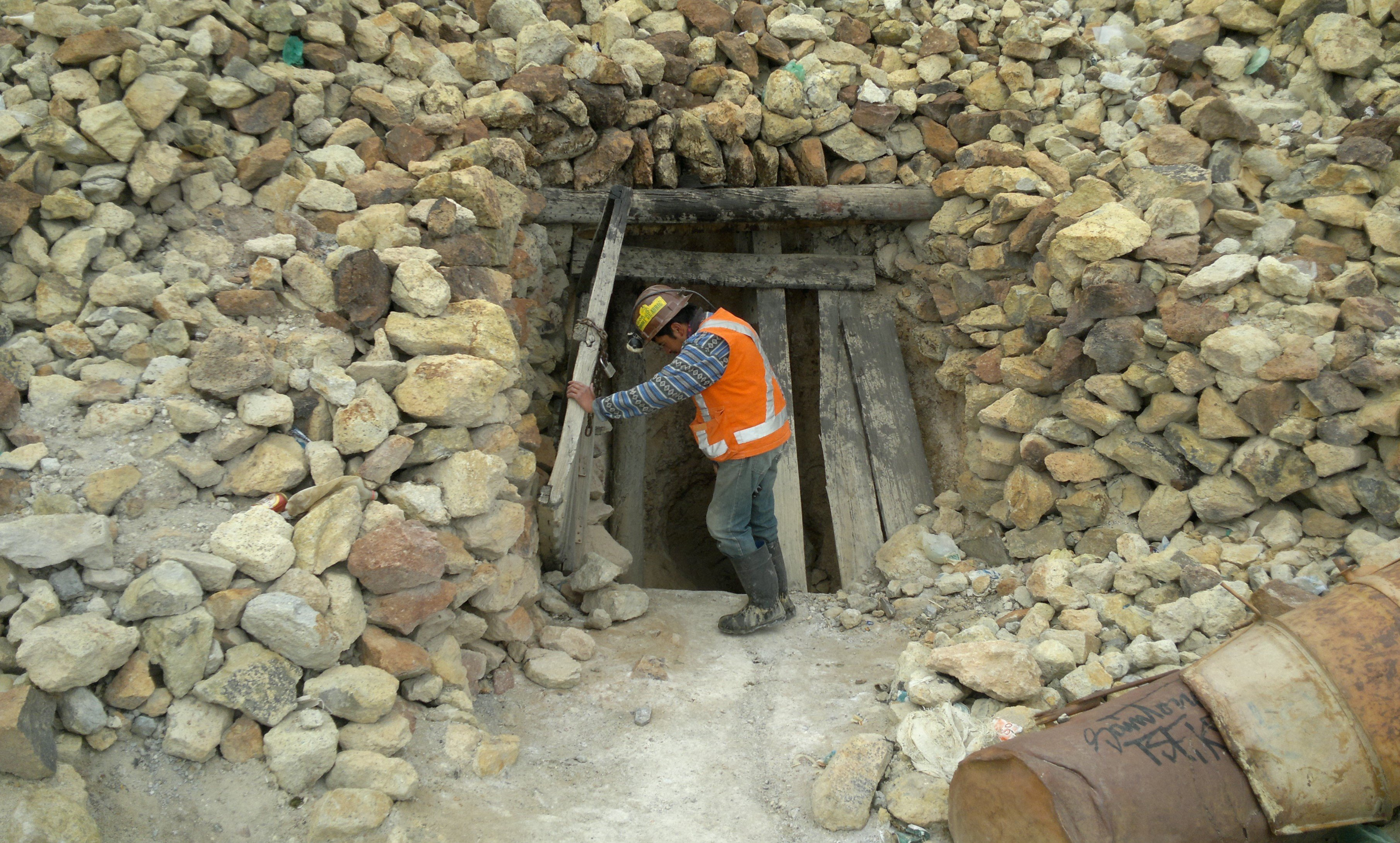 """Miner opening the doors of a silver mine in """"Cerro Rico"""", Potosí, Bolivia."""